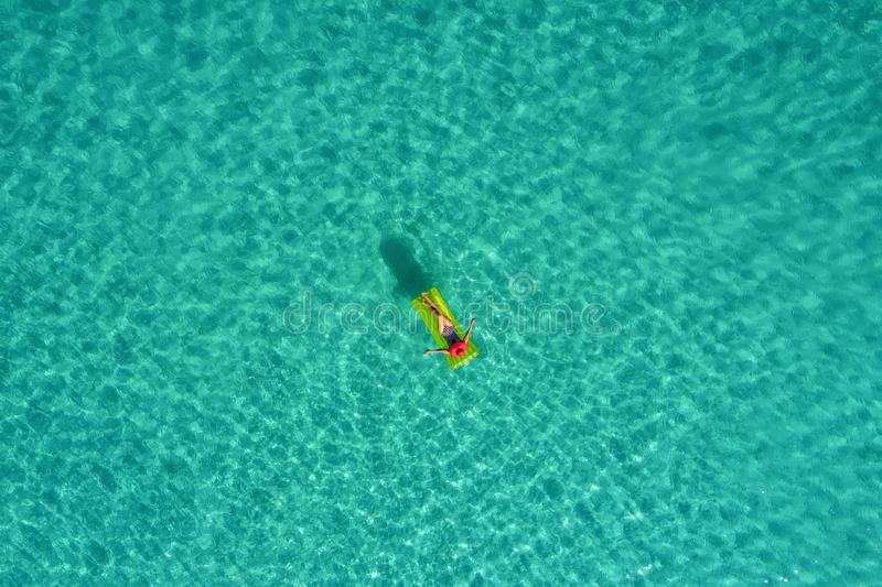 Aerial view of slim woman swimming on the swim mattress in the transparent turquoise sea in Seychelles. Summer seascape with girl. Beautiful waves, colorful stock images