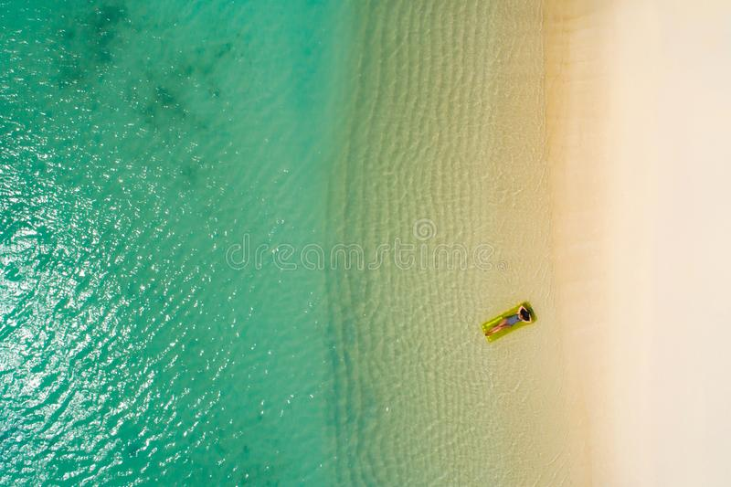 Aerial view of slim woman swimming on the swim mattress in the transparent turquoise sea in Seychelles. Summer seascape with girl. Beautiful waves, colorful stock photo