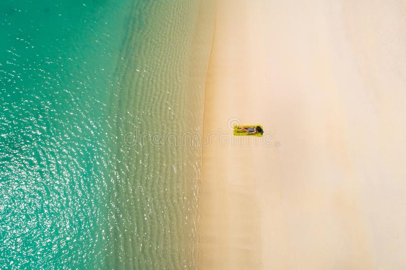 Aerial view of slim woman swimming on the swim mattress in the transparent turquoise sea in Seychelles. Summer seascape with girl. Beautiful waves, colorful stock image