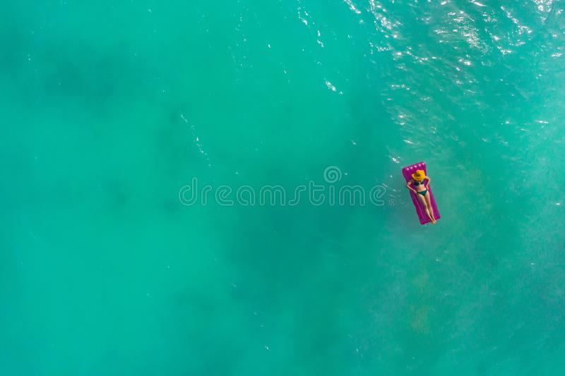 Aerial view of slim woman swimming on the swim mattress in the transparent turquoise sea. Summer seascape with girl, beautiful. Waves, colorful water. Top view stock images