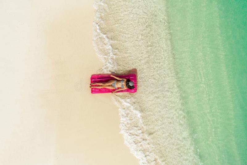 Aerial view of slim woman swimming on the swim mattress in the transparent turquoise sea. Summer seascape with girl, beautiful stock image