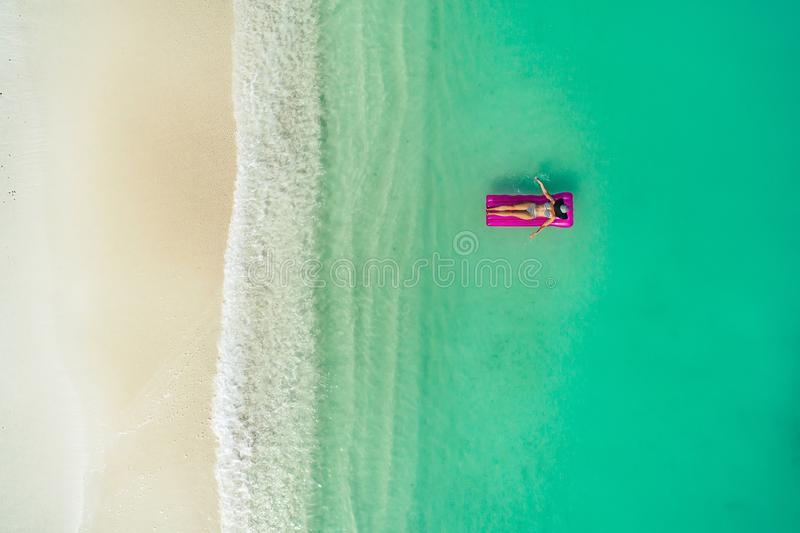 Aerial view of slim woman swimming on the swim mattress in the transparent turquoise sea. Summer seascape with girl, beautiful. Waves, colorful water. Top view stock image