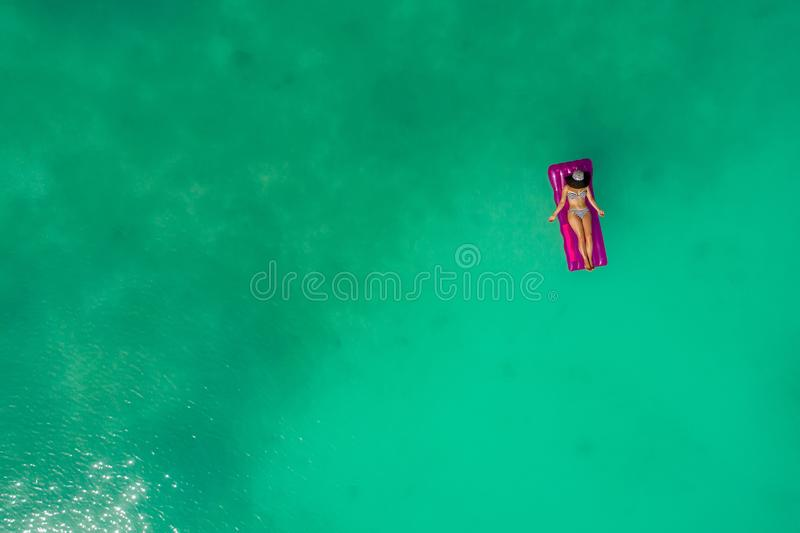 Aerial view of slim woman swimming on the swim mattress in the transparent turquoise sea. Summer seascape with girl, beautiful. Waves, colorful water. Top view stock photos