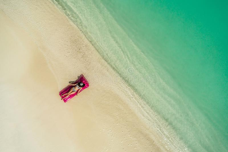 Aerial view of slim woman swimming on the swim mattress in the transparent turquoise sea. Summer seascape with girl, beautiful. Waves, colorful water. Top view royalty free stock photo