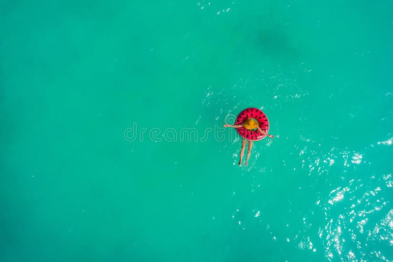 Aerial view of slim woman swimming on the swim ring  donut in the transparent turquoise sea. Summer seascape with girl, beautiful. Waves, colorful water. Top royalty free stock photo