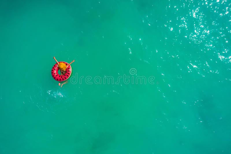 Aerial view of slim woman swimming on the swim ring  donut in the transparent turquoise sea. Summer seascape with girl, beautiful. Waves, colorful water. Top stock images