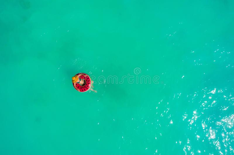Aerial view of slim woman swimming on the swim ring  donut in the transparent turquoise sea. Summer seascape with girl, beautiful. Waves, colorful water. Top royalty free stock image