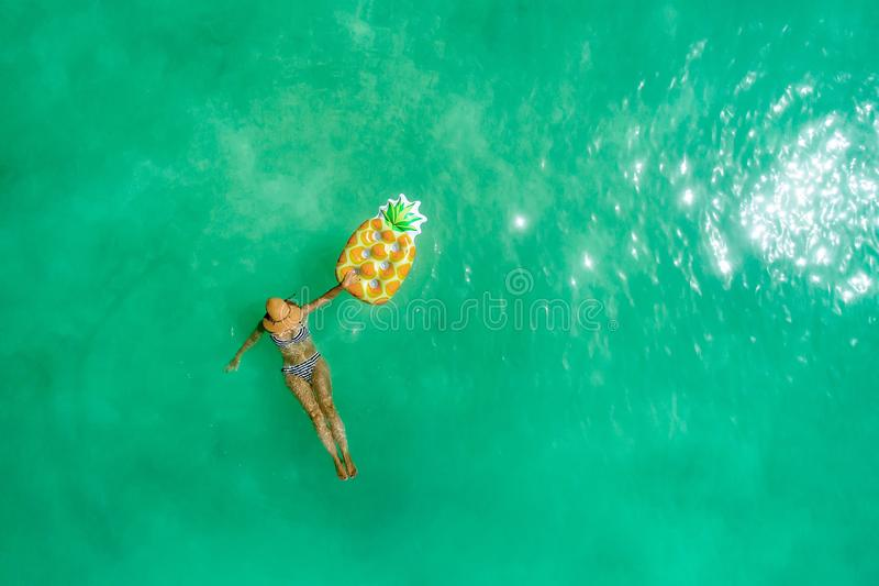 Aerial view of slim woman swimming on the transparent turquoise sea. Summer seascape with girl, beautiful waves, colorful water. Top view from drone stock photography