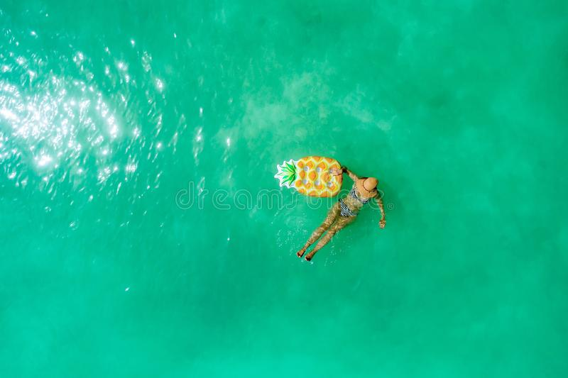 Aerial view of slim woman swimming on the transparent turquoise sea. Summer seascape with girl, beautiful waves, colorful water. royalty free stock photos