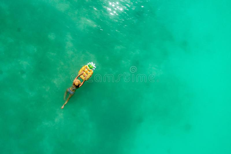Aerial view of slim woman swimming on the transparent turquoise sea. Summer seascape with girl, beautiful waves, colorful water. Top view from drone stock images