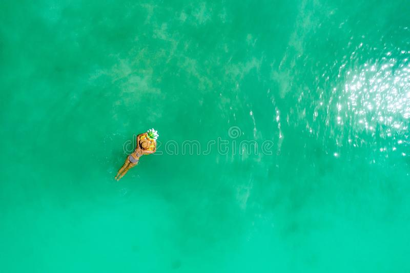 Aerial view of slim woman swimming on the transparent turquoise sea. Summer seascape with girl, beautiful waves, colorful water. Top view from drone royalty free stock image
