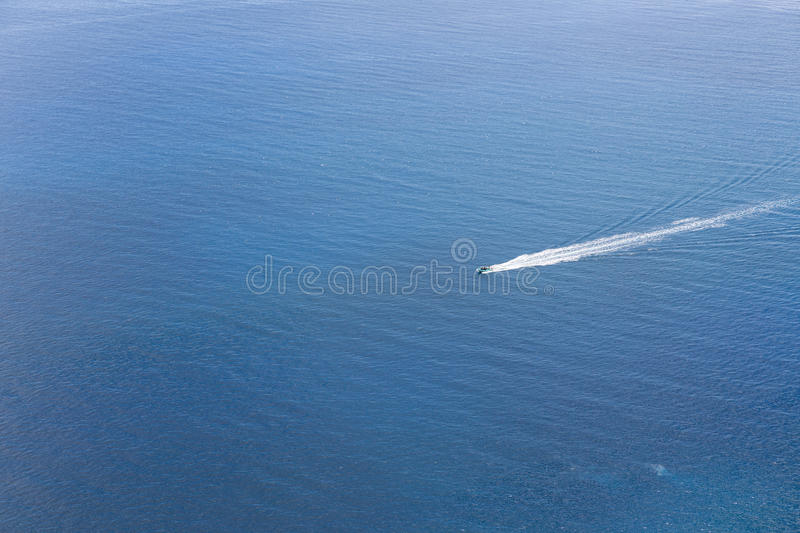 Aerial view of a small ship navigating at a blue ocean royalty free stock photography