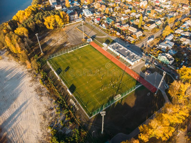 Aerial view of small soccer or football stadium with green lawn in city landscape, drone photo.  stock photos