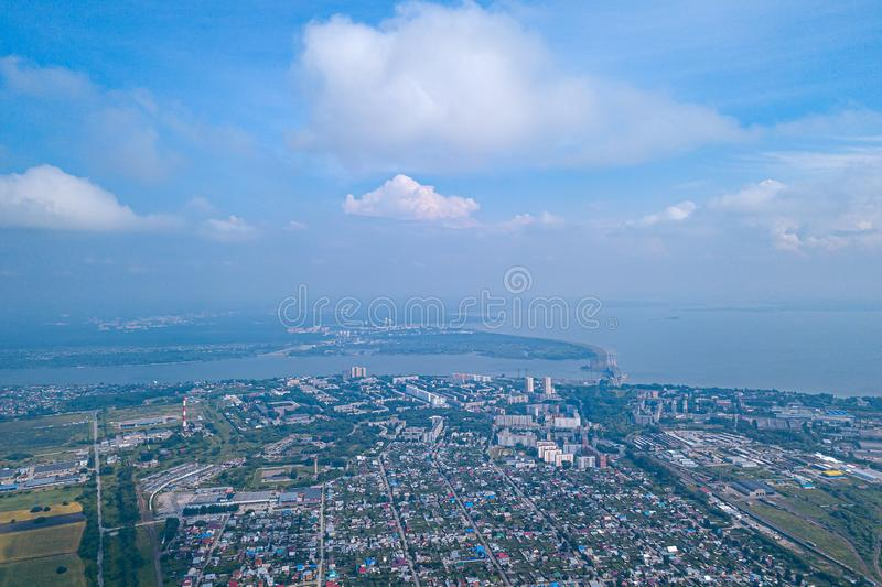 Aerial view of a small town with low-rise buildings and houses in the sky at the height of gray clouds with a river and the sea on. The horizon royalty free stock photography