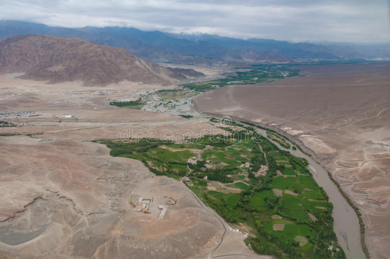 Aerial view of a small village and river creek in a green valley surrounded by rocky desert mountains. Aerial view of village settlement in the green valley with stock photography