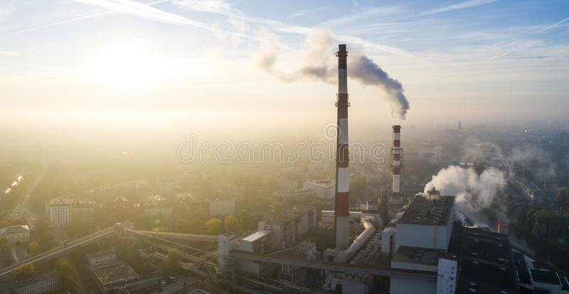 Aerial view of the smog over the city in the morning, smoking chimneys of the CHP plant and the city`s buildings stock images