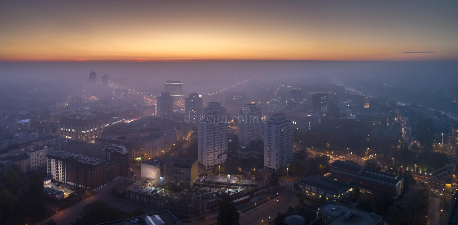 Aerial view of the smog over the waking city at dawn, buildings covered with fog and smog royalty free stock photo