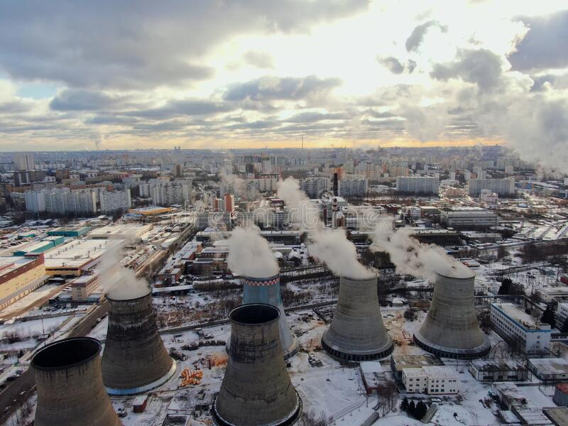 Aerial view smokestacks plant polluting air in the metropolis on a sunny day in winter. Environmental safety of the big city stock photo
