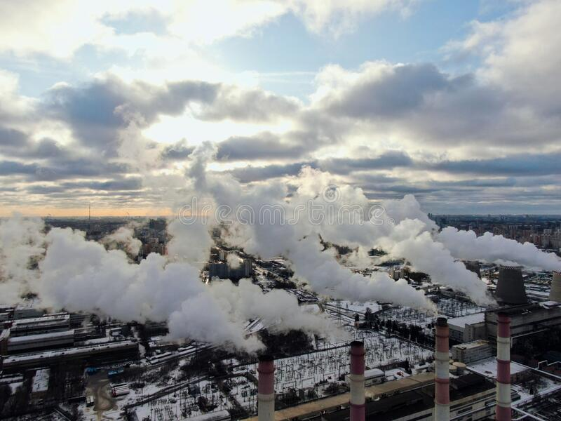 Aerial view smokestacks plant polluting air in the metropolis on a sunny day in winter. Environmental safety of the big city royalty free stock photo