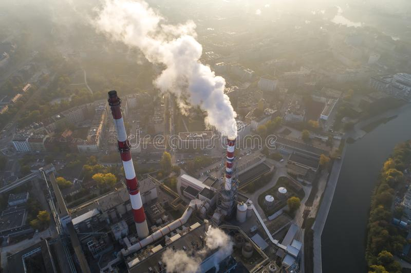 Aerial view of smoking chimneys of CHP plant and smog over the city and builidings in the background royalty free stock photo