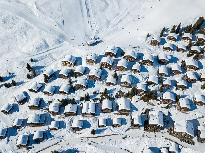Aerial view of snow covered roofs over the traditional chalets. With skiing lift station in the village of Swiss alps stock photography