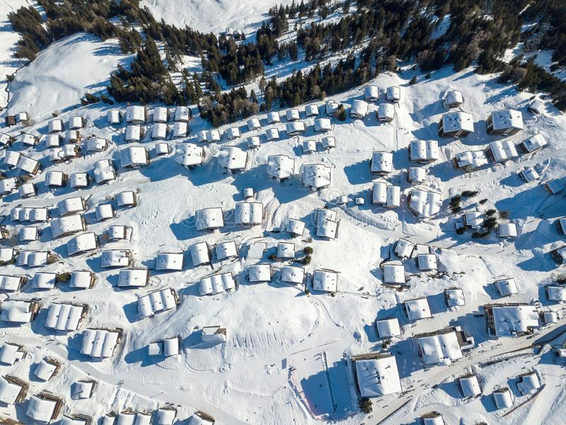 Aerial view of snow covered roofs over the traditional chalets. In the village of Swiss alps stock image