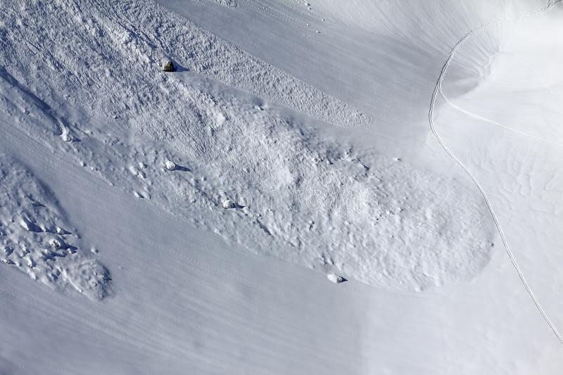 Aerial view of snow slope with trace of avalanche and ski track. Dangerous conditions royalty free stock images