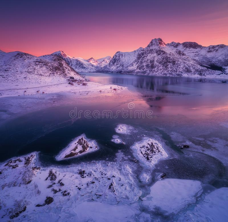 Aerial view of snowy mountains, blue sea with frosty coast. Reflection in water and purple sky at colorful sunset in Lofoten islands, Norway. Winter landscape stock photography