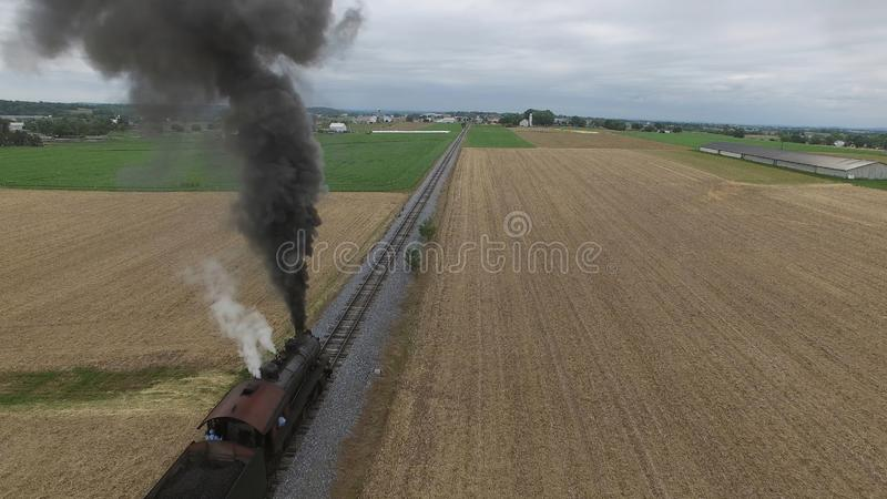 Steam Passenger Train Puffing Smoke in amish Countryside 9. Aerial View of a Steam Passenger Train Puffing Smoke in Amish Countryside on a Sunny Spring Day stock images