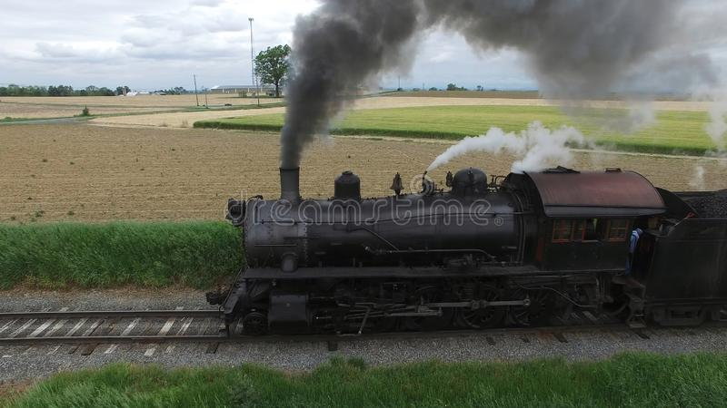 Steam Passenger Train Puffing Smoke in amish Countryside 3. Aerial View of a Steam Passenger Train Puffing Smoke in Amish Countryside on a Sunny Spring Day royalty free stock images