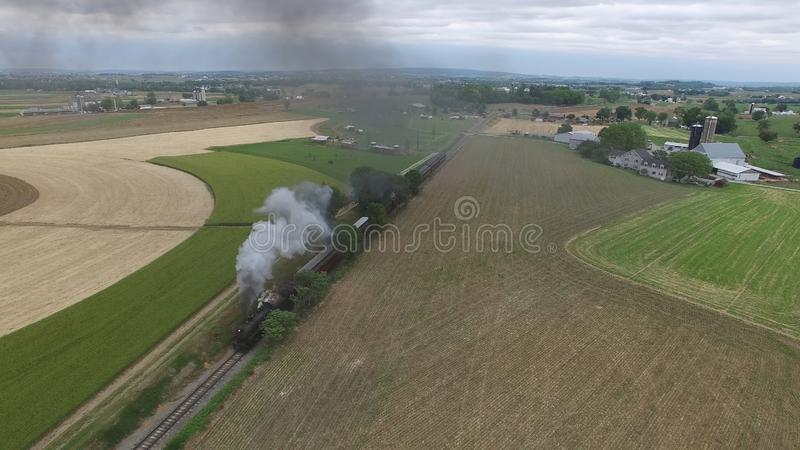 Steam Passenger Train Puffing Smoke in amish Countryside 12. Aerial View of a Steam Passenger Train Puffing Smoke in Amish Countryside on a Sunny Spring Day royalty free stock image