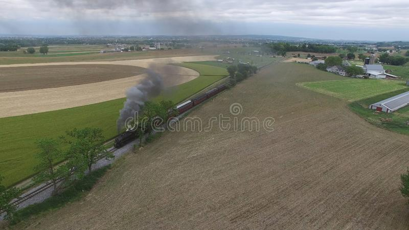 Steam Passenger Train Puffing Smoke in amish Countryside 14. Aerial View of a Steam Passenger Train Puffing Smoke in Amish Countryside on a Sunny Spring Day royalty free stock image
