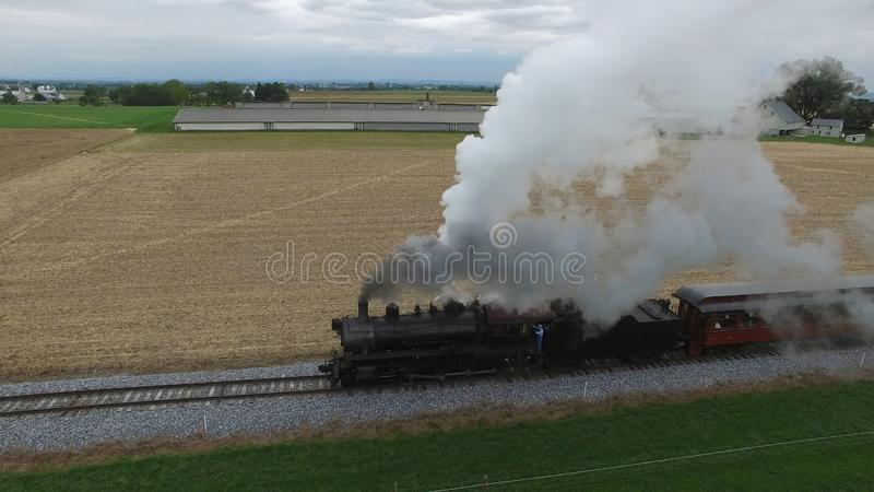 Steam Passenger Train Puffing Smoke in amish Countryside 19. Aerial View of a Steam Passenger Train Puffing Smoke in Amish Countryside on a Sunny Spring Day stock photo