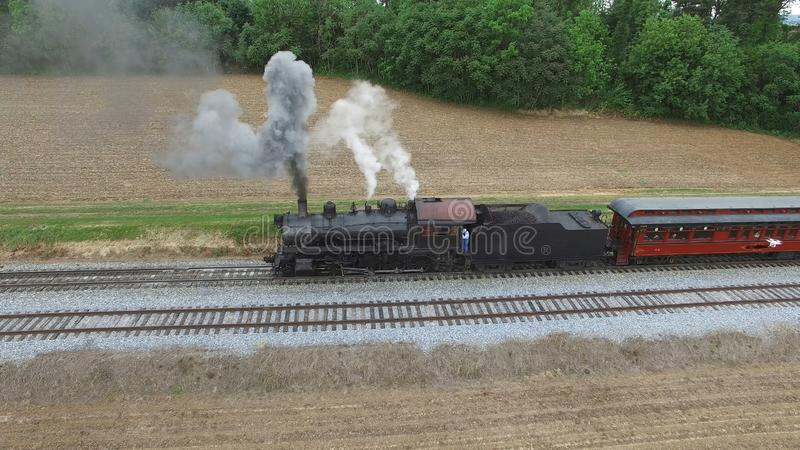 Steam Passenger Train Puffing Smoke in amish Countryside 27. Aerial View of a Steam Passenger Train Puffing Smoke in Amish Countryside on a Sunny Spring Day stock photos