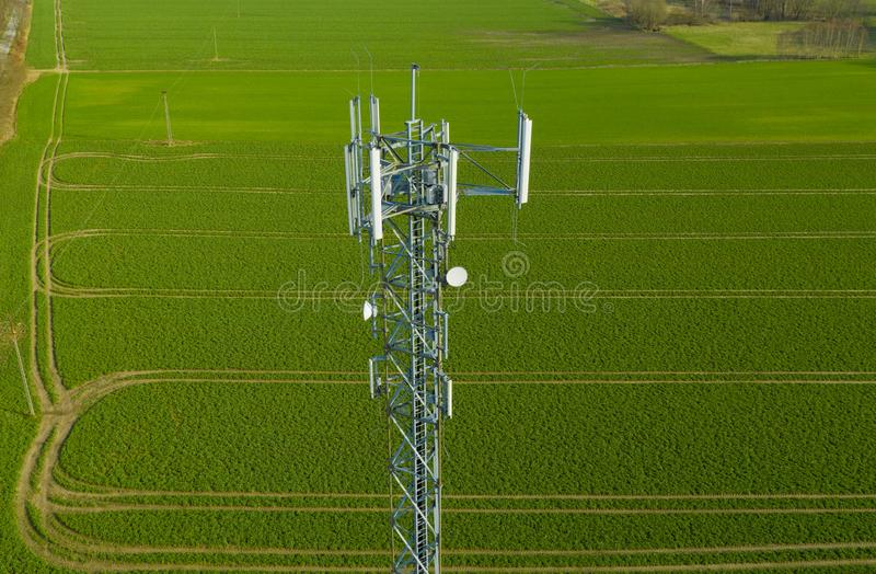 Aerial view on steel telecommunication tower in the middle of green field transmitting radio, telephone and internet signal stock images