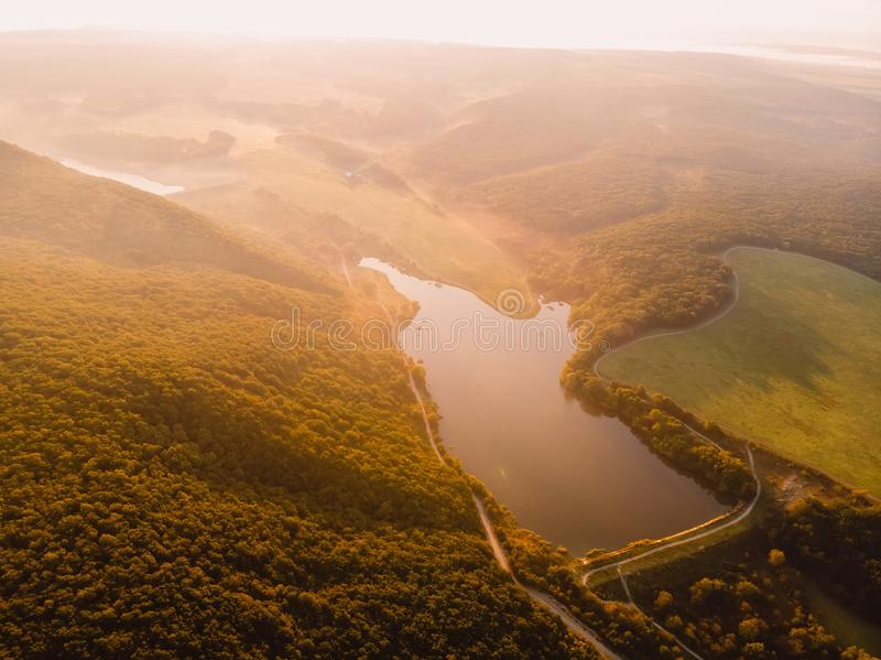Aerial view of still water lake and warm sunset or sunrise with fog royalty free stock photography