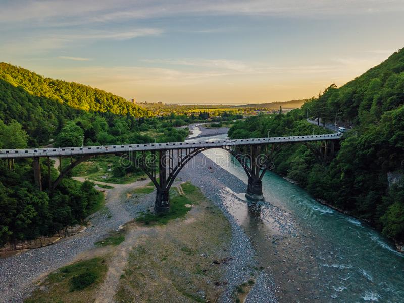 Aerial view of stone bridge over gorge of river Gumista, Abkhazia. Above mountain river flowing in the forest. View from drone royalty free stock photo