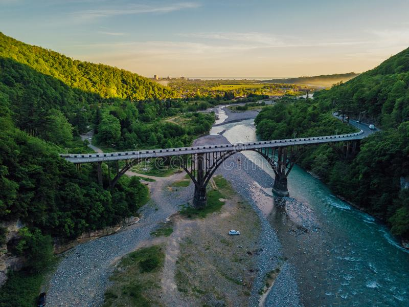 Aerial view of stone bridge over gorge of river Gumista, Abkhazia. Above mountain river flowing in the forest. View from drone stock photo