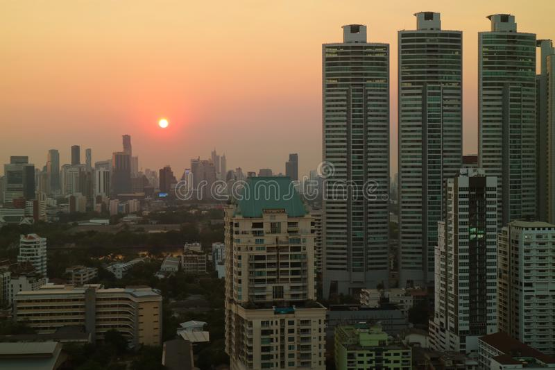 Aerial view of the sun setting amongst skyscrapers in Bangkok downtown royalty free stock images