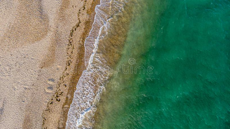 An aerial view of a sunny sandy beach with crashing waves and green crystal water stock images