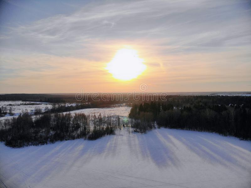 Aerial view of the sunset on a winter freezing evening. Beautiful picturesque landscape of snowy forest and field. Aerial, view, sunset, winter, freezing stock images