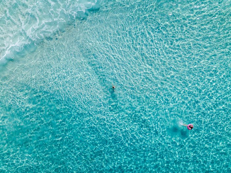 Aerial shot of swimmers on a beautiful beach with blue water and white sand - deep water. Aerial view of swimmers on a beautiful beach with white sand and blue stock photo