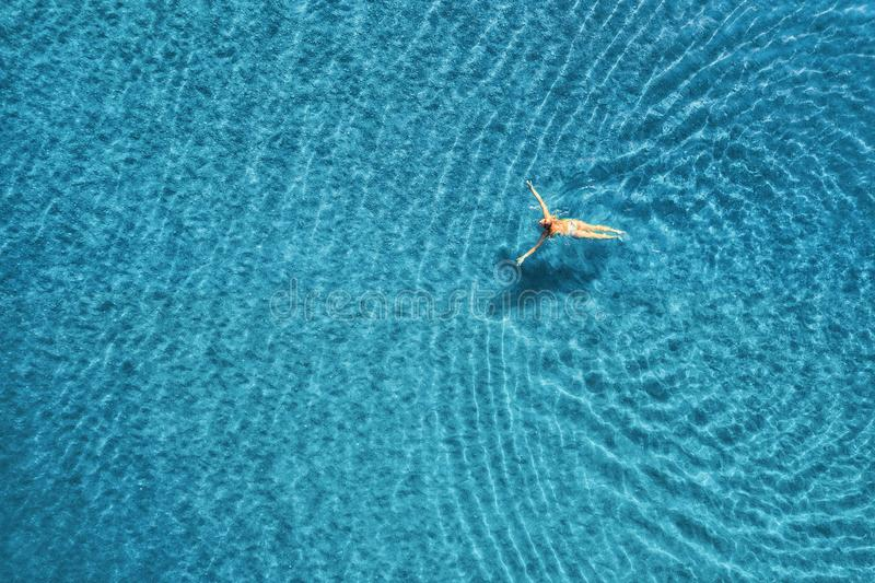 Aerial view of swimming woman in the sea at sunset in Maldives. Aerial seascape with young girl, clear blue water, waves in summer. Transparent water. Top view stock images