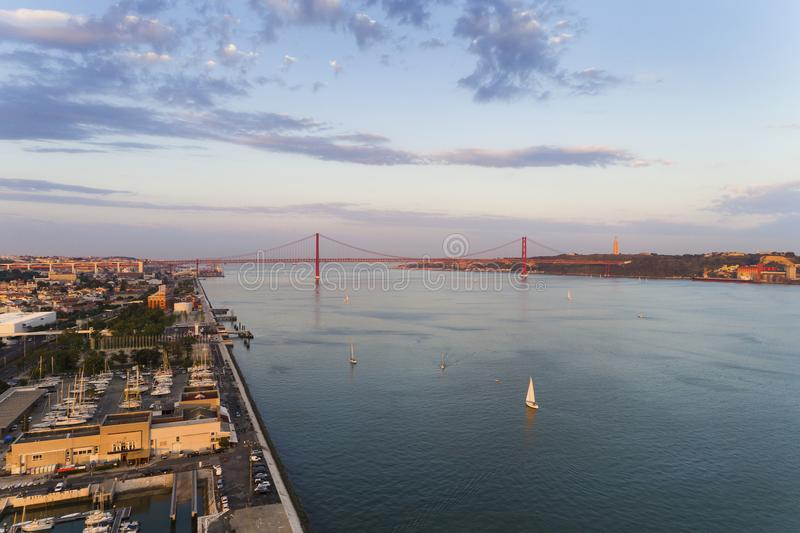 Aerial view of the Tagus River RIo Tejo in the city of Lisbon with sail boats and the 25 of April Bridge on the background;. Concept for travel in Portugal and royalty free stock photo