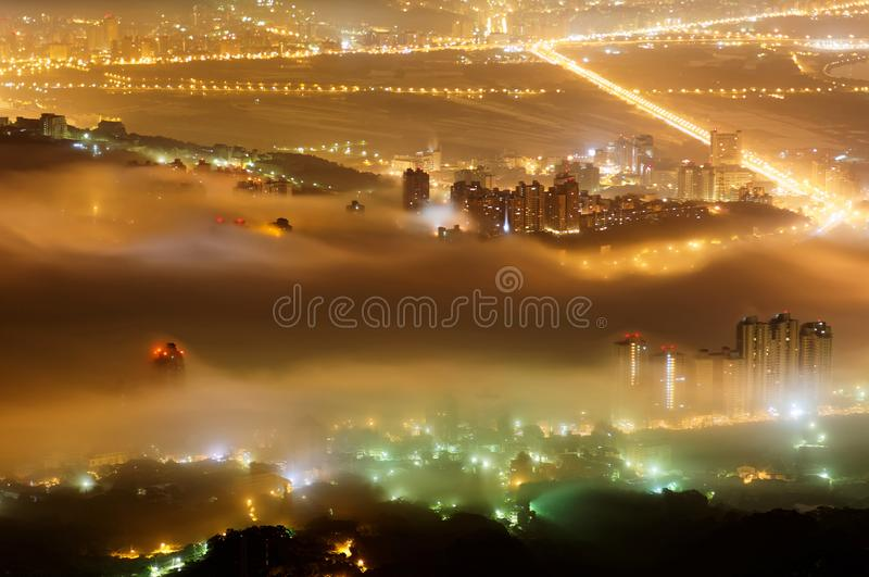 Aerial view of Taipei on a foggy evening, the vibrant capital city of Taiwan, with colorful lights of buildings. & streets glistening in the mist ~Scenery royalty free stock photo
