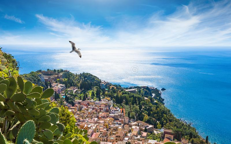 Aerial view of Taormina resort town located in Metropolitan City of Messina, on east coast of Sicily island, Italy. Bright sun in blue sky, azure sea and green royalty free stock image