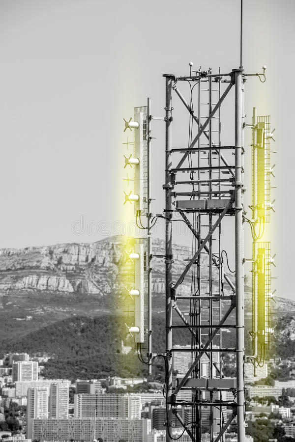 Aerial view of telecommunication tower black and white yellow li. Aerial view of telecommunication tower with multiple antennas and data transmitters with light royalty free stock photos
