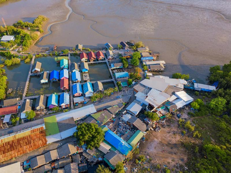 Aerial view of Thai traditional Asian fishing village near sea beach. Floating houses at sunset background in rural area, Phuket stock photo