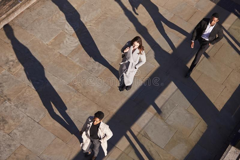 Aerial view of three business people walking in the same direction on a sunny urban street, horizontal royalty free stock photography