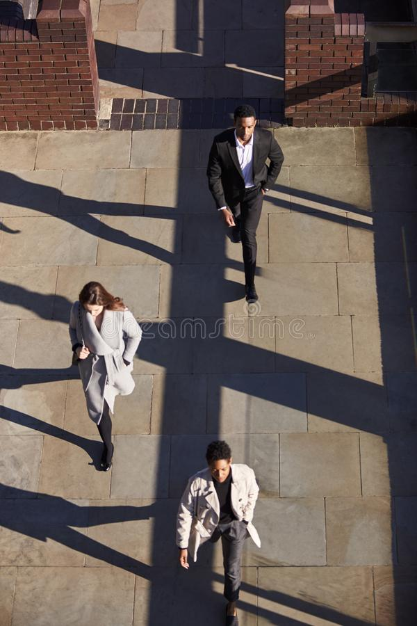 Aerial view of three business people walking in the same direction on a sunny urban street, vertical royalty free stock photos